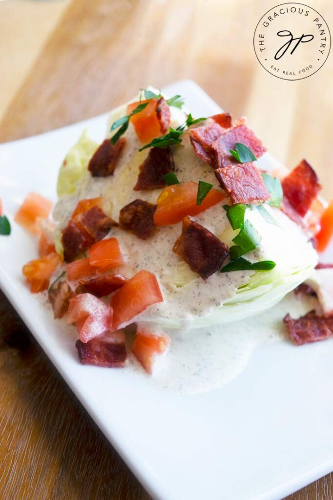 A traditional wedge salad on a white plate with dressing, bacon bits, tomatoes and fresh herbs.