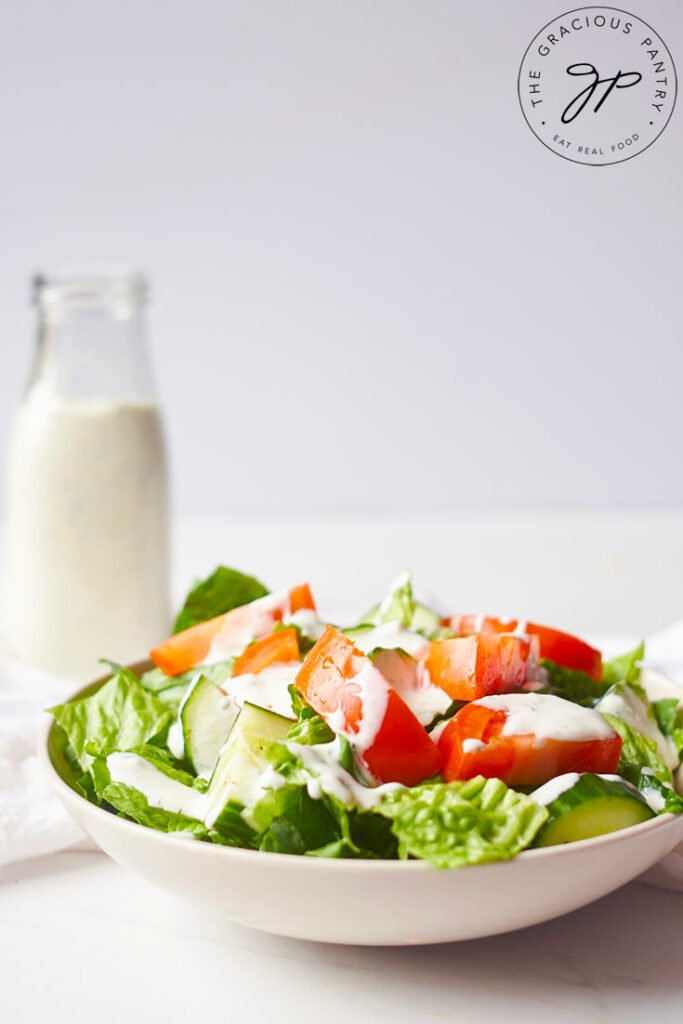 A green salad with cut cucumbers and tomatoes in a white bowl with Buttermilk Ranch Dressing drizzled over the top.