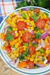 A side view of this Cajun Corn Salad Recipe in a bowl on a table.