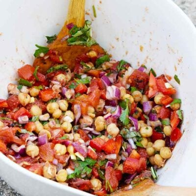 A side view of a white mixing bowl filled with this Chickpea Salad Recipe.