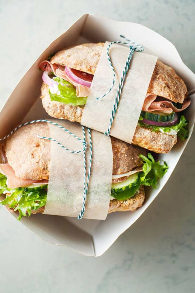 A guide to healthy lunches. Two whole grain sandwiches, wrapped with a parchment strip and ribbon, witting in a sandwich box.