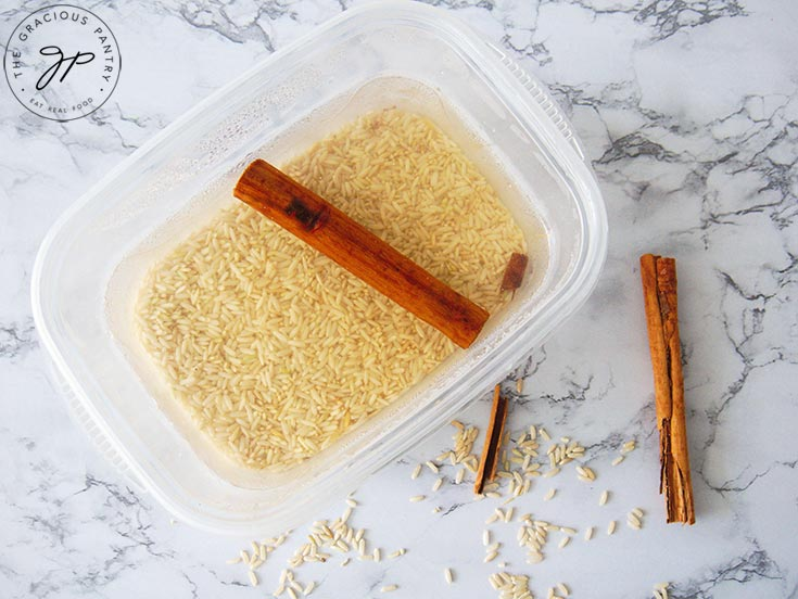 Combining the rice, water and cinnamon in a soaking container.