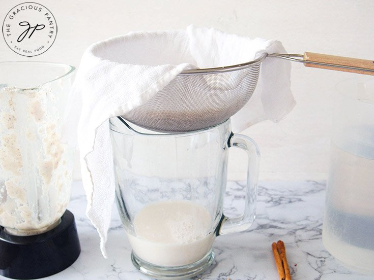 Straining the blended rice through a sieve with a cheesecloth.