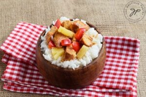 The finished Slow Cooker Pineapple Chicken, served over rice in a wooden bowl. The bowl sits on a red and white checkered towel.