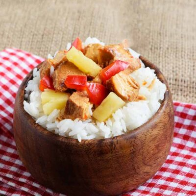 Slow Cooker Pineapple Chicken served in a wood bowl over rice, sitting on a table.
