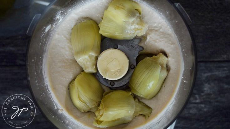 Adding the artichoke hearts to the food processor.