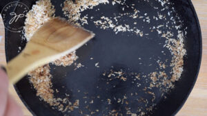 Browning the shredded coconut in a dry pan for topping the coconut cream version of this Coconut Meringue Pie Recipe.