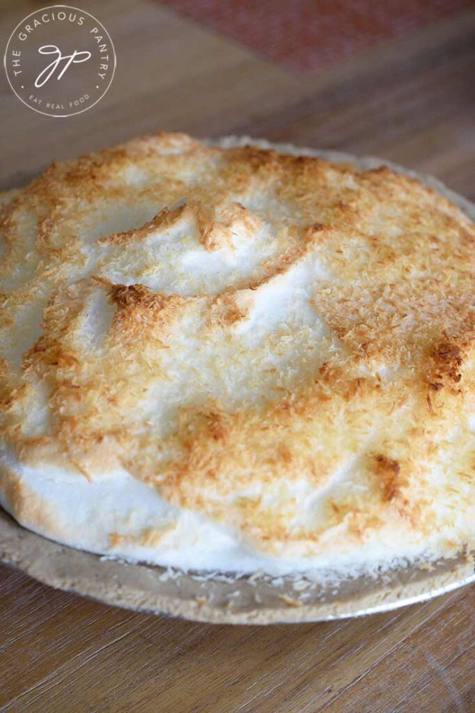 A front view of a whole, coconut meringue pie, just out of the oven.