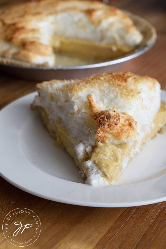 A single slice of Coconut Meringue Pie Recipe on a plate, with the whole pie sitting behind it.