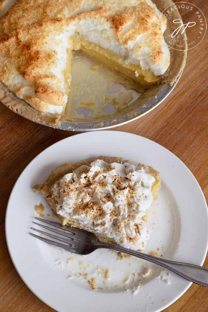 And overhead shot of a half eaten slice of coconut cream pie, with a whole coconut meringue pie sitting behind it.