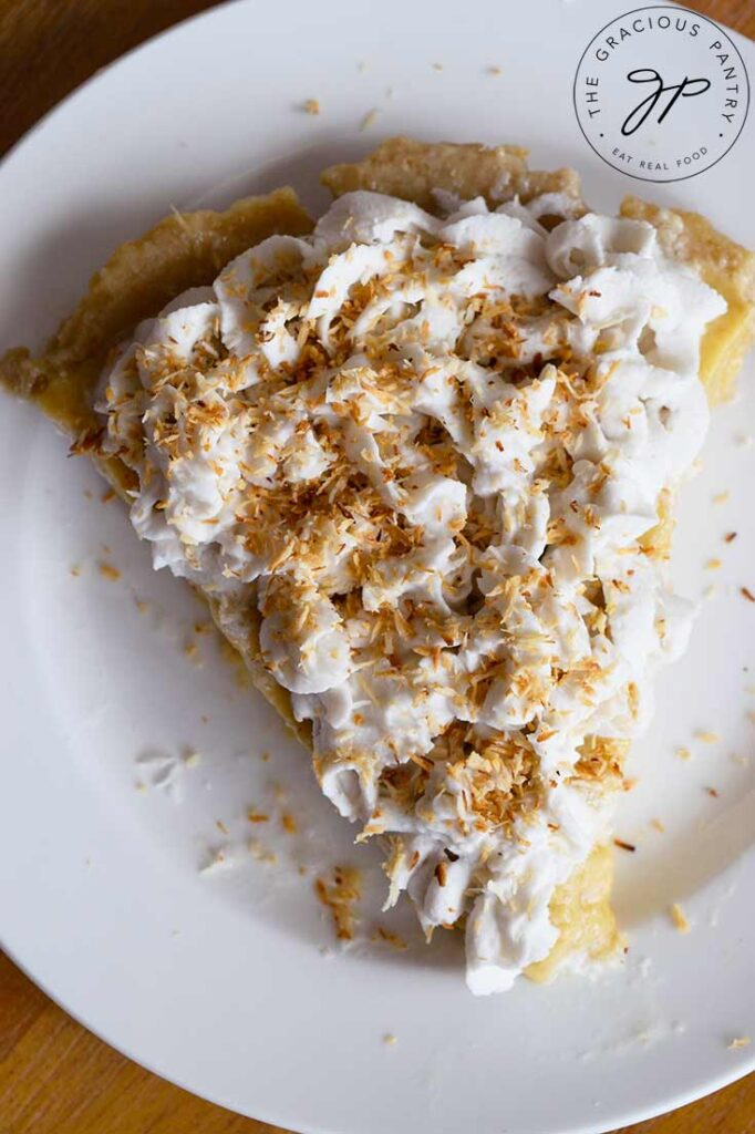 And overhead view of a single slice of coconut cream pie on a white plate.