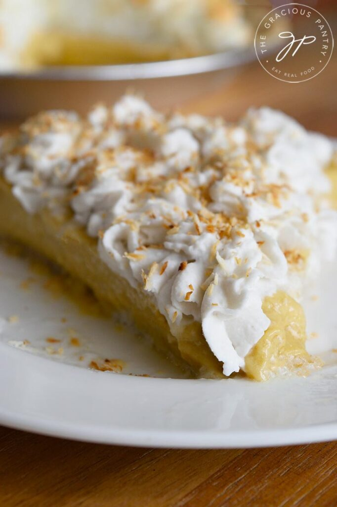 A front view of a single slice of coconut cream pie with roasted cocoanut sprinkled on top.