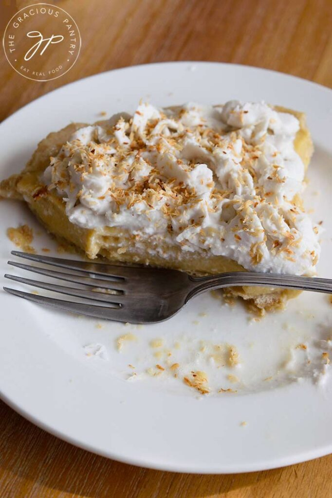 A half eaten slice of coconut cream pie with a fork resting next to the slice on the plate.