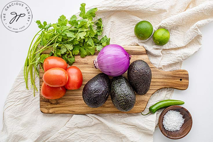 Guacamole Recipe ingredients collected on a cutting board.