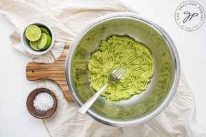 Mashed avocado in a metal mixing bowl.