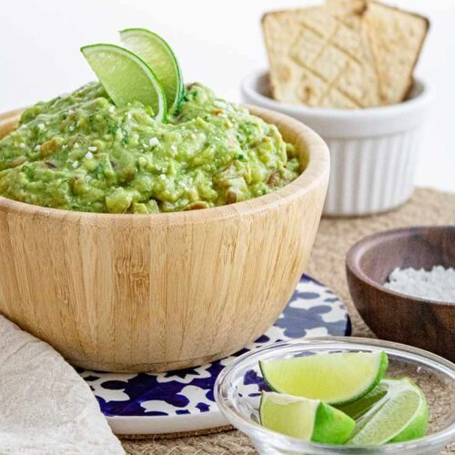 A side view of a wooden bowl filled with guacamole. Lime wedges sit in a small bowl in front.