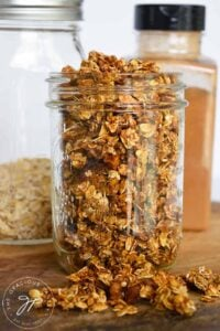 An up close shot of granola in a canning jar. A bottle of cinnamon sits behind it.