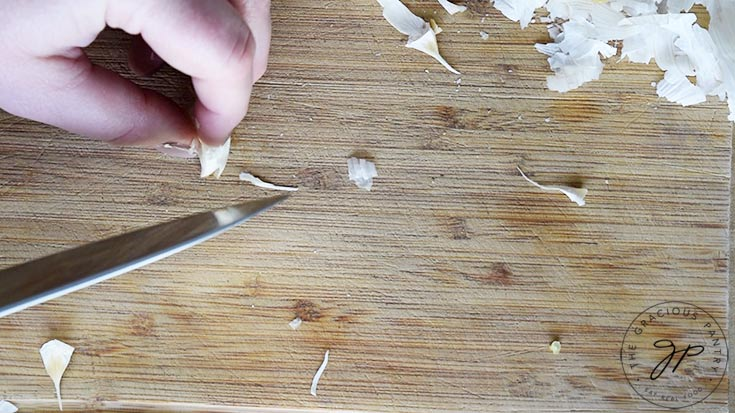 Cutting the tip off a garlic clove that wasn't cut the first time around.