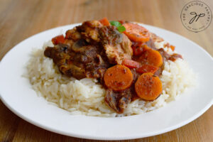 The finished Slow Cooker Chicken Cacciatore served over rice on a white plate.