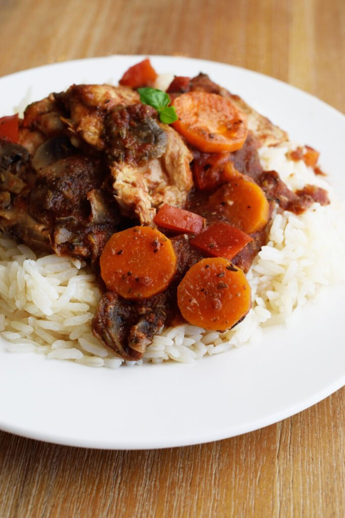 Slow Cooker Chicken Cacciatore served over a bed or rice on a white plate.
