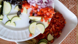 The cut vegetables being added to the cooked pasta in a large, white mixing bowl.