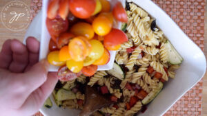 Stirring the cut tomatoes into the pasta salad.