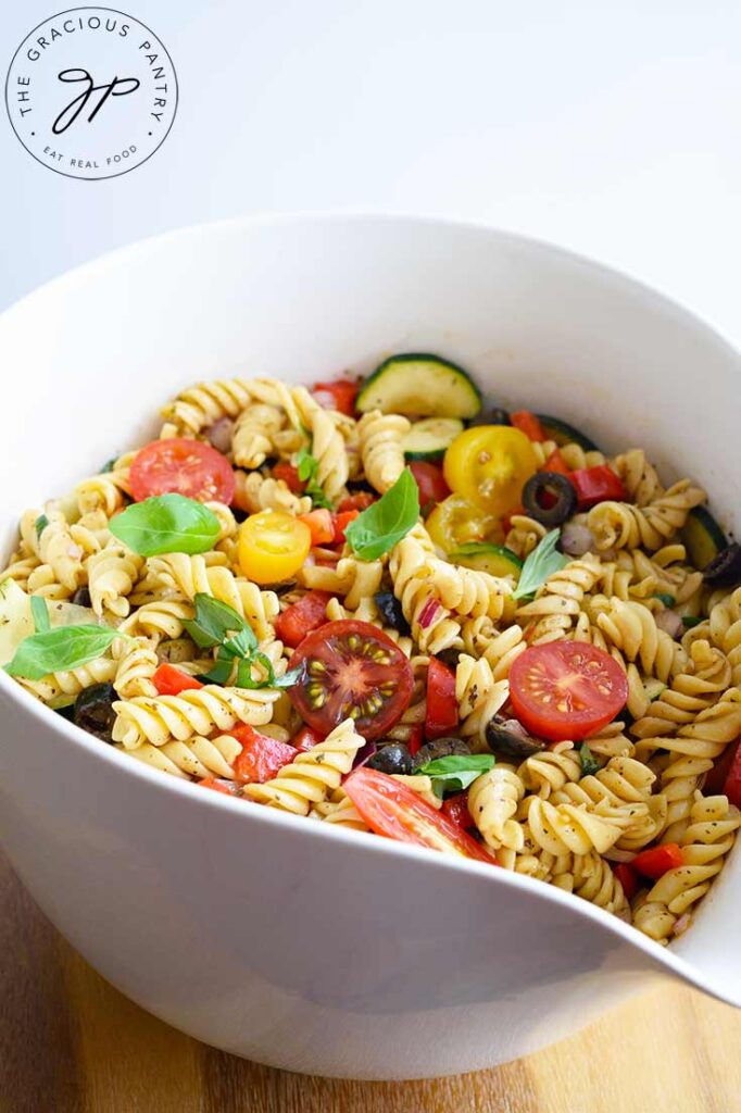 Pasta mixed with tomatoes, zucchini, black olives and fresh basil, fill a white mixing bowl.