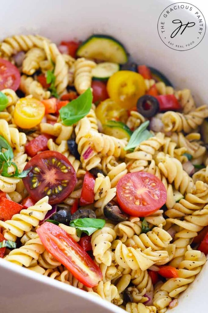 A micro shot of this Vegetable Pasta Salad shows pasta, tomatoes, basil and zucchini.