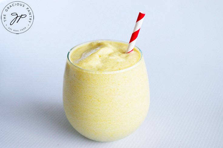 The finished Virgin Pina Colada Recipe in a stemless wine glass with a red and white stripped straw.