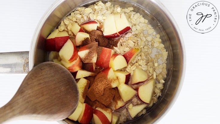 Combining all the ingredients for this Apple Pie Oatmeal Recipe in a small pot to cook.