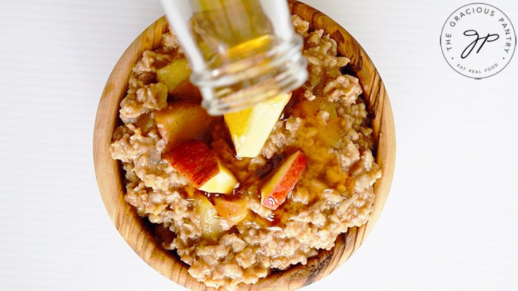 Pouring maple syrup over the finished Apple Pie Oatmeal in a wooden bowl.