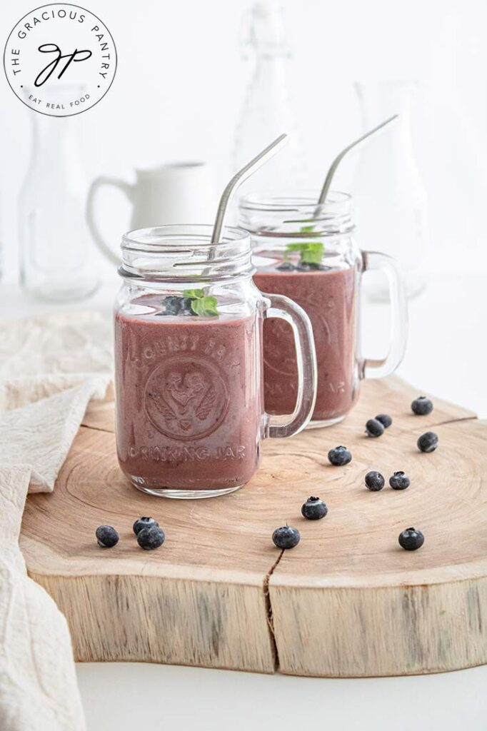 A side view of two glass canning jar mugs filled with this Acai Smoothie.