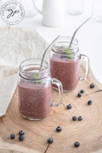 Two glass mugs filled with Acai Smoothie. Fresh berries lay around the base of the jar.