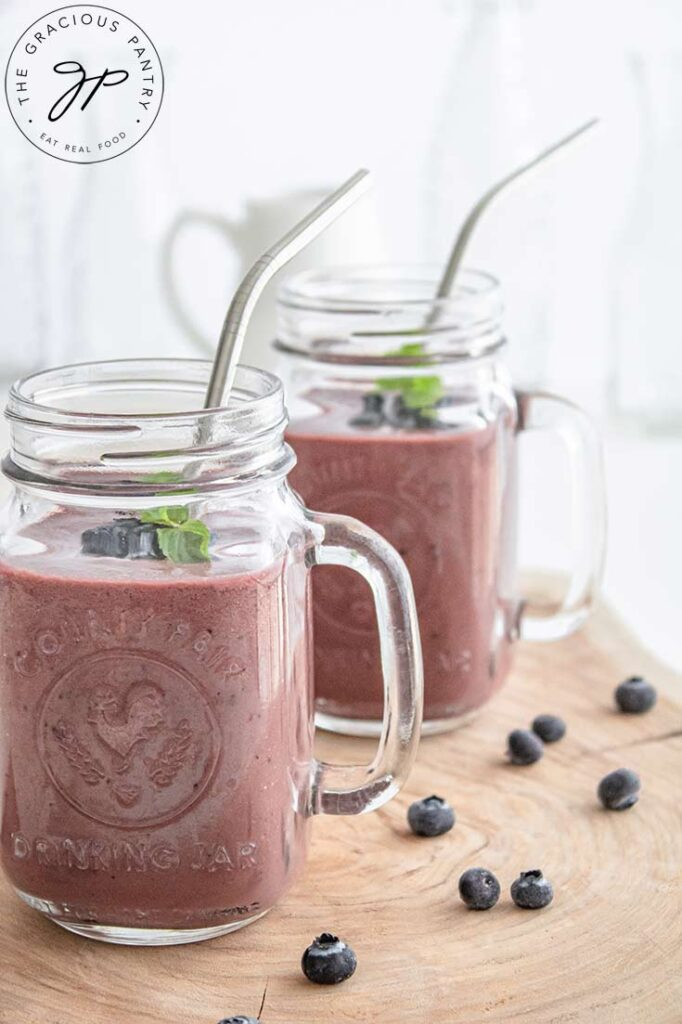 An up close shot of mugs filled with this smoothie and topped with mint leaves and metal straws.