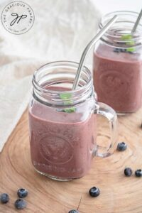 Two glass mugs sit on a wooden surface with a towel behind them, filled with Acai Smoothie.