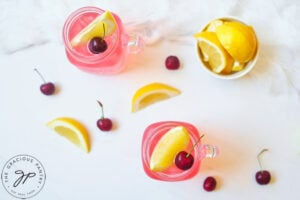 An overhead shot looking down at two glass mugs filled with Cherry Green Tea Lemonade. A small bowl of lemon wedges sits to the side.