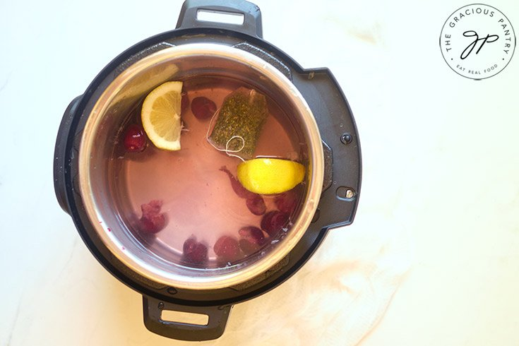 A horizontal shot of a tea back, cherries and lemons in an instant pot.
