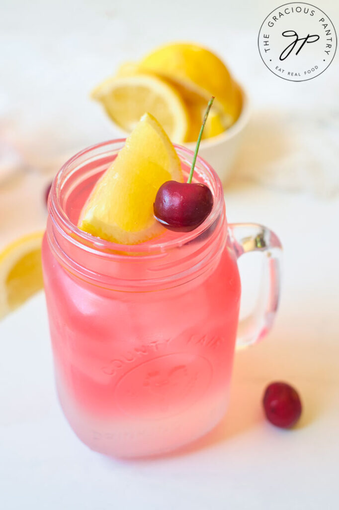 A single glass mug filled with Cherry Green Tea Lemonade and topped with a lemon wedge and a cherry.