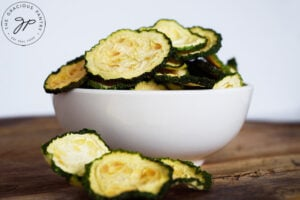 The finished Dehydrated Zucchini Chips in a small, white serving bowl.