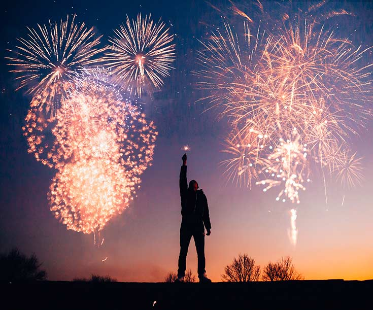 Man stands in shadow holding a sparkler with fireworks going off behind him.