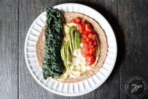 A tortilla with hummus and kale, sliced avocado, chopped onions and tomatoes covering the layer of hummus underneath.