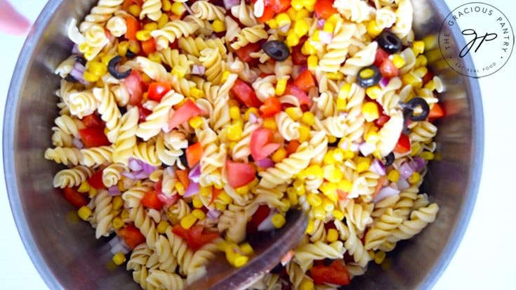 Mixing all the Mexican Pasta Salad ingredients into the pasta.