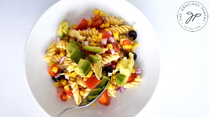 Serving chunks of avocado over the Mexican Pasta Salad in a white serving bowl.