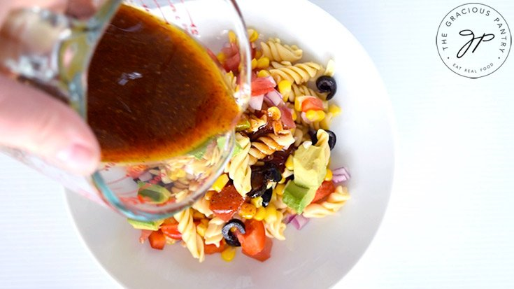 Pouring the dressing over the Mexican Pasta Salad.