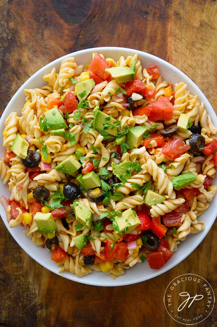 An overhead shot looking down into a white bowl filled with this Mexican Pasta Salad. The bowl sits on a wooden surface.
