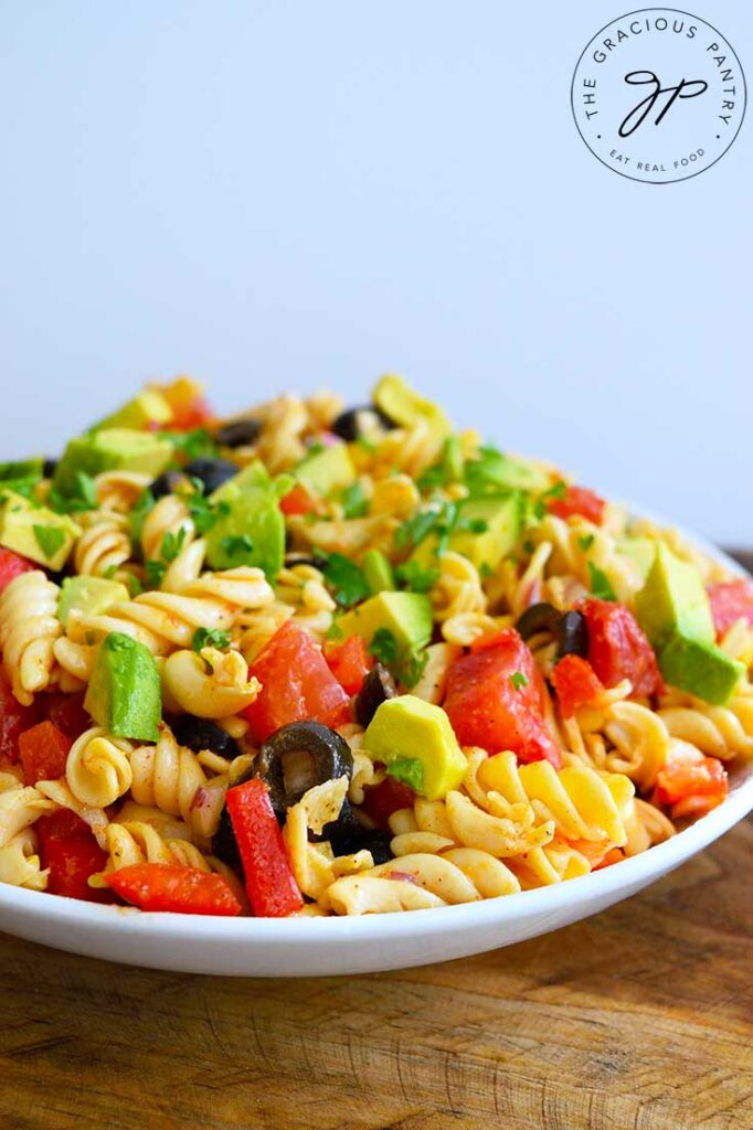 A side view of a white bowl filled with this Mexican Pasta Salad.