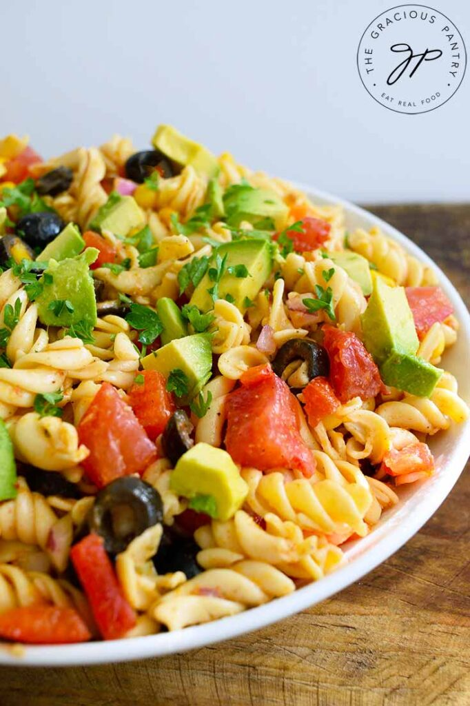 An up close shot of a white bowl completely filled with this Mexican Pasta Salad, against a white background.