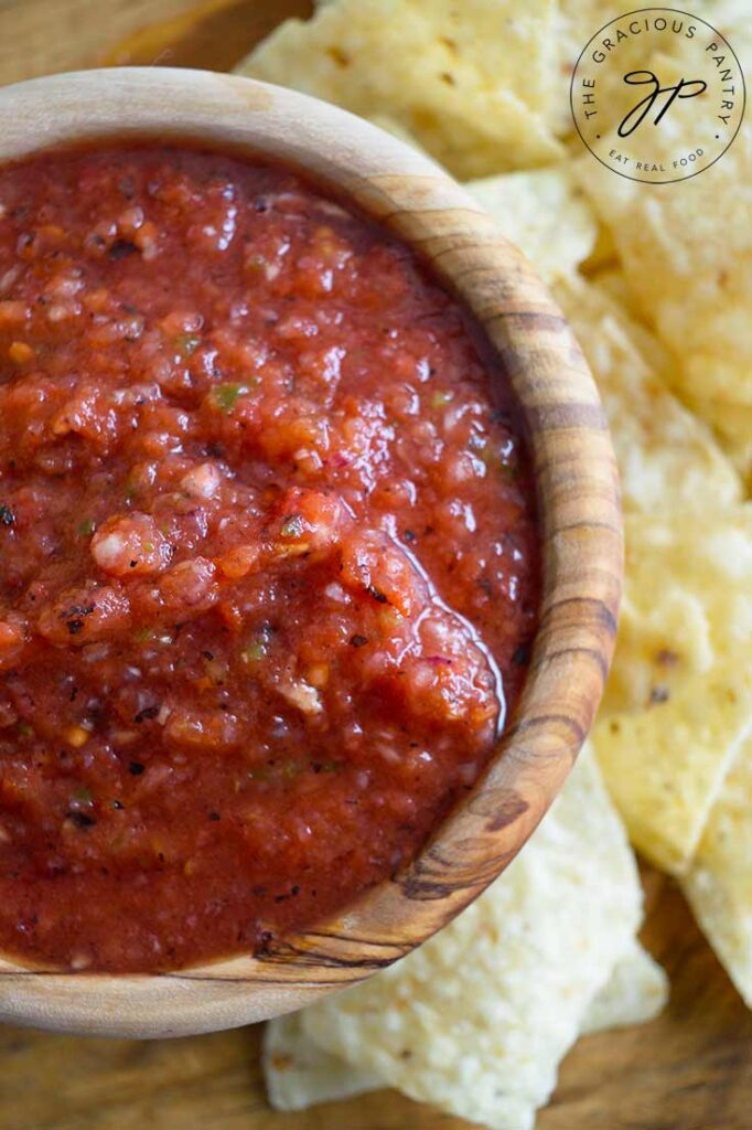And overhead view of restaurant salsa in a wooden bowl with corn chips laying on the side.