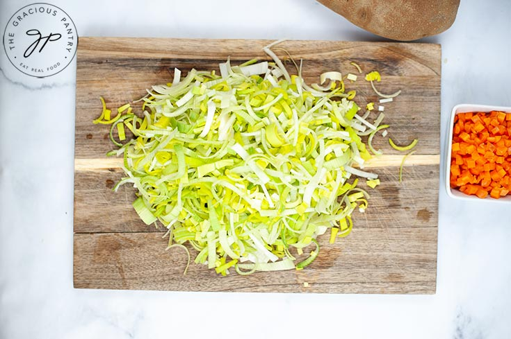 The finely cut leeks in a pile on a cutting board.