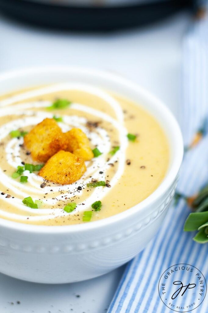 An up close shot of a bowl of Instant Pot Potato Leek Soup, topped with croutons and a swirl of cream.